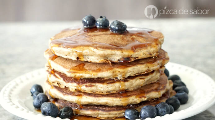A stack of oat pancakes sit on a plate with blueberries on top